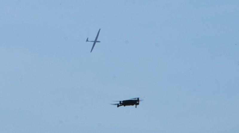 Segelflugzeug am Himmel mit Drohne im Vordergrund